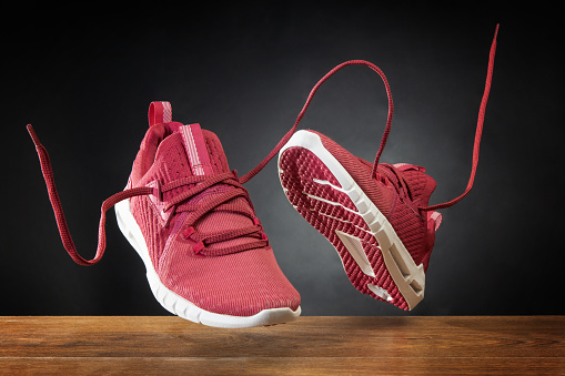 Flying in the air pink running sports shoes. Abstract shopping concept. Levitation sports shoes with flying laces