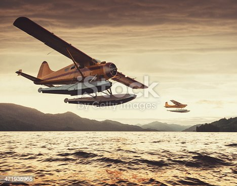 Two float planes at low altitude in sunset light over an Alaskan inlet.  Shot at high iso with light grain.