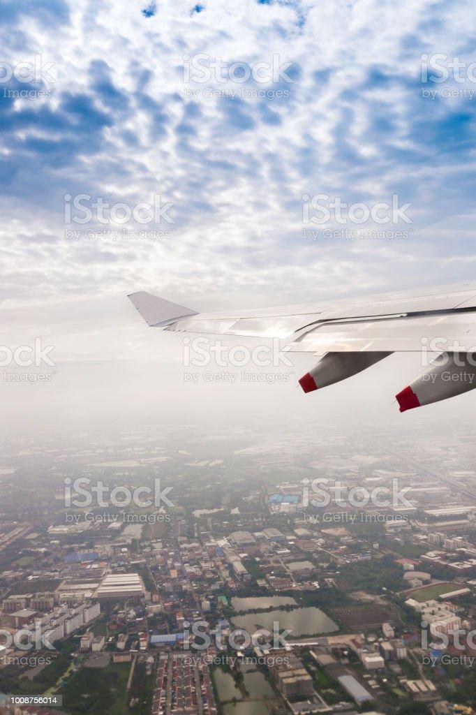 Voando para o céu azul e asa de avião com a paisagem urbana de vista superior do avião de janela - foto de acervo