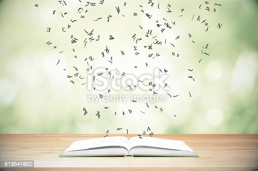 istock Flying letters from the opened book on wooden table 513541602