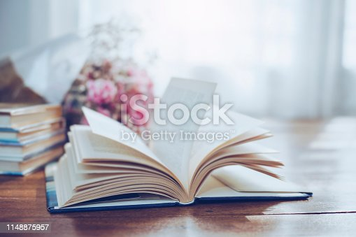 flying and blurred open page of old book with flowers on wooden background