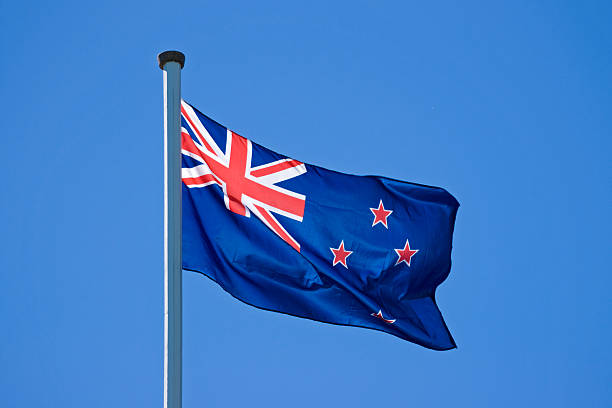flying new zealand flag - new zealand flag stock photos and pictures