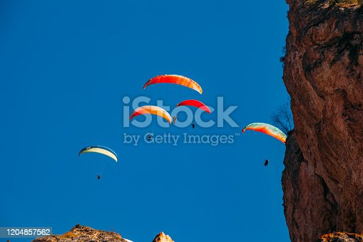 Flying of paragliders above autumn rocky mountains.