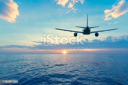 istock Flying of the passenger plane above the sea surface. 1194587554
