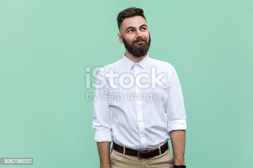 istock Flying of thoughts. Thoughtful bearded businessman looking away while standing against light green wall. Studio shot 836798032