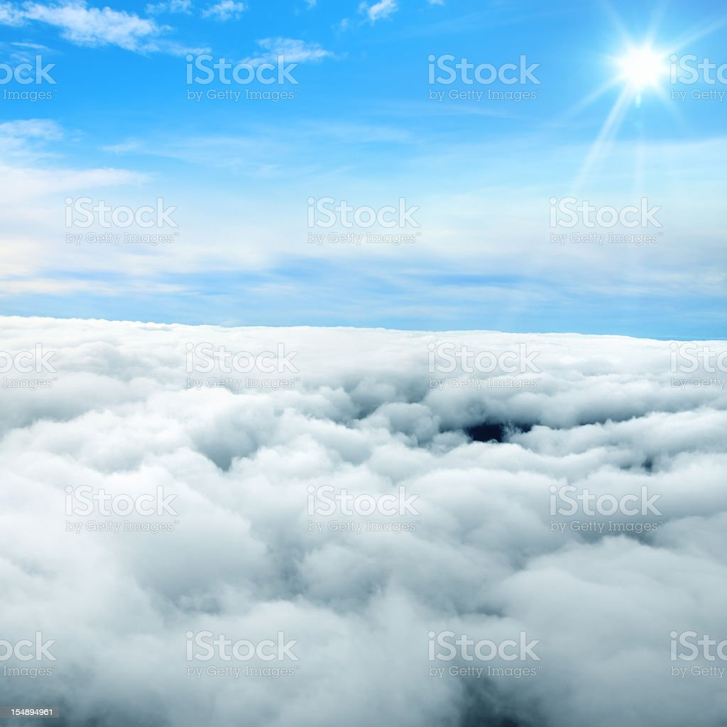 sun shining over blue sky above the stormy clouds.