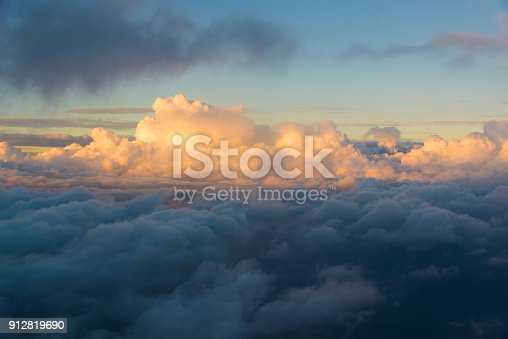 istock Flying over the clouds at sunset 912819690