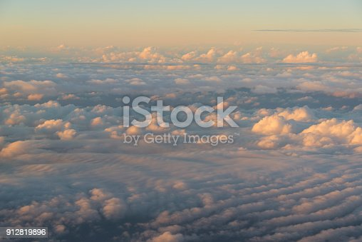 istock Flying over the clouds at sunset 912819896