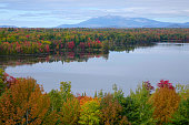 AERIAL: Flying over the spectacular autumn colored forest and towards the lake. High mountain overlooking the vast colorful woods in picturesque New Hampshire. Breathtaking natural beauty in the fall.