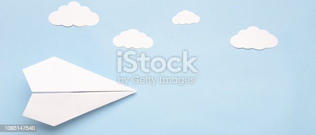 istock Flying paper plane in the clouds on a blue background. Concept of flight, travel, transfer. Top view, copy space, flat lay, banner 1065147540