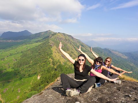 Three beautiful young woman flying on top of mountain above Munnar Tea fields on around 1600 m above sea level in the Western Ghats range of mountains in the southwestern state of Kerala, India. It is part of UNESCO World Heritage Site as one of the eight hottest places of biological diversity in the world.