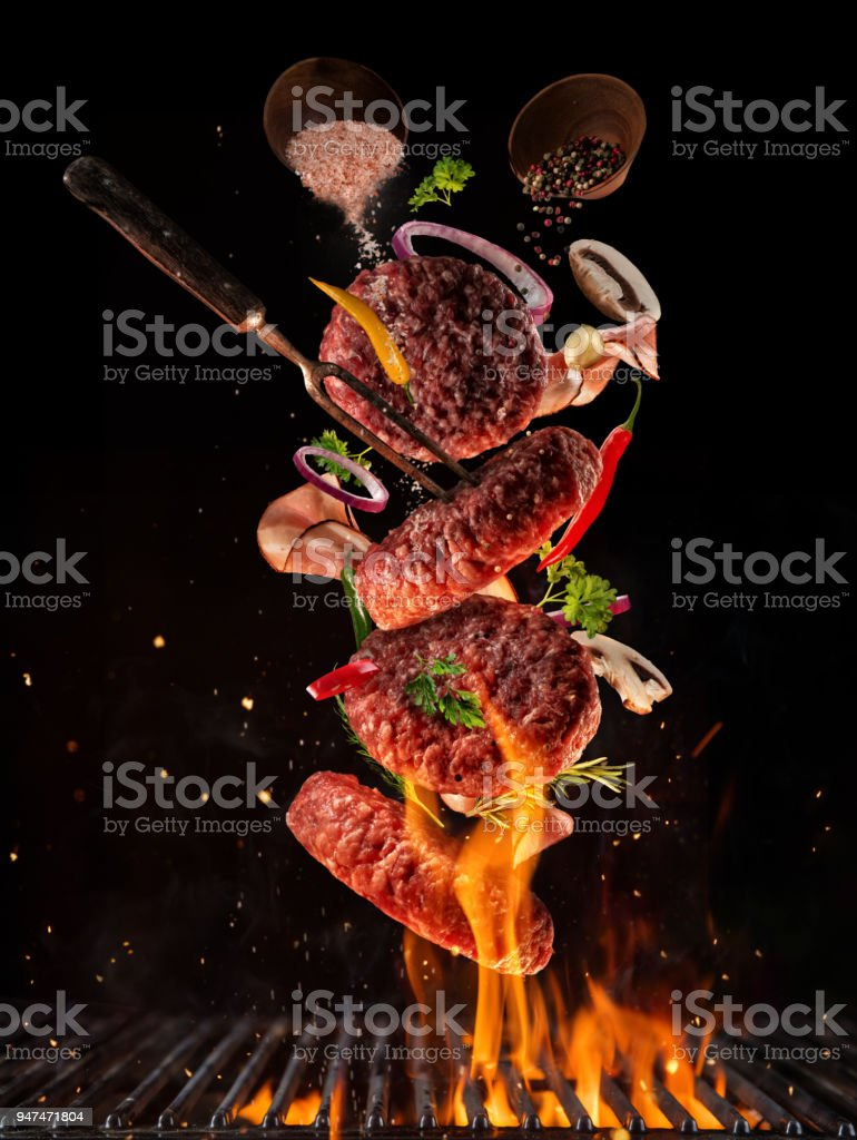 Flying pieces of beef meat pieces on hamburger from grill stock photo