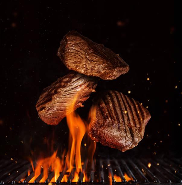 vliegende stukken rundvlees rump steaks op zwart - vleesdelen stockfoto's en -beelden