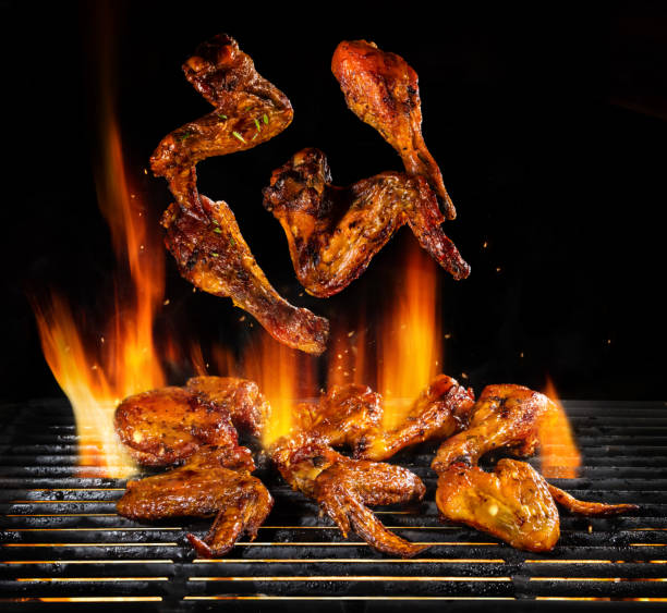 flying pieces of chicken meat on grill - ala di animale foto e immagini stock