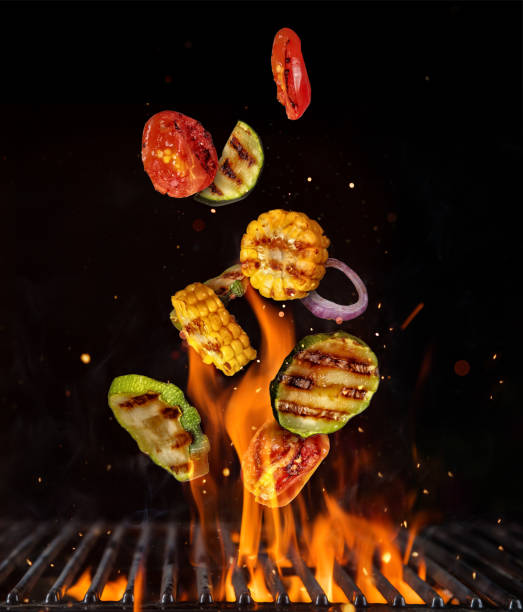 flying pieces of vegetable from grill grid, isolated on black background - grilled vegetables stock photos and pictures
