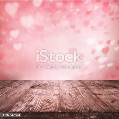 Flying pink hearts for valentines day. Abstract background and empty wooden table for a romantic love concept with space for design and text.