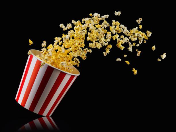 vliegende popcorn uit gestreepte emmer geïsoleerd op zwarte achtergrond - popcorn stockfoto's en -beelden
