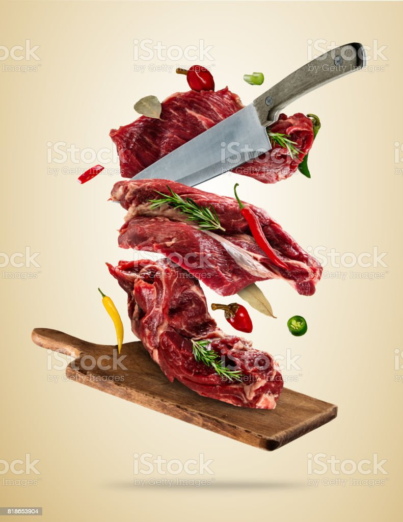 Flying raw steaks with ingredients, food preparation concept stock photo