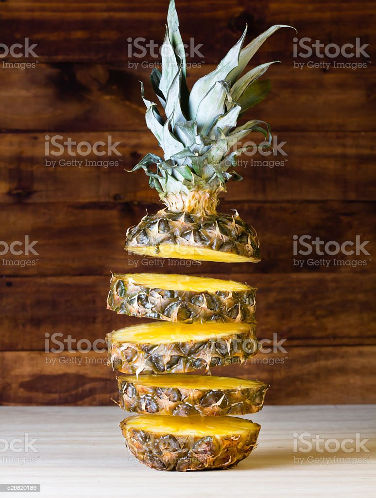Flying slices of pineapple on wooden background. Closeup stock photo