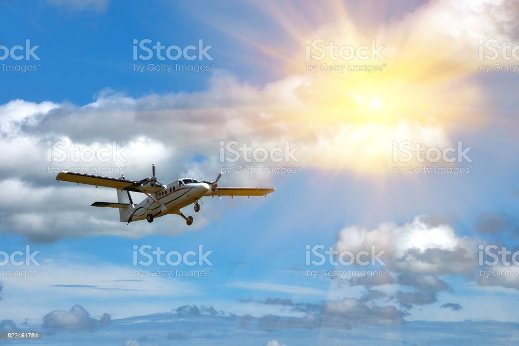 Flying small passenger propeller plane in flight on a lovely sunny day stock photo