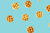 Flying small round waffles isolated on trendy blue background. Minimal food and bakery concept, modern and contemporary style