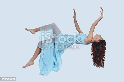 Studio shot of attractive young woman in elegant dress keeping arms outstretched while hovering against grey background