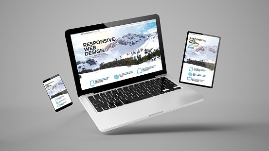 istock flying tablet, laptop and mobile phone showing responsive web design 1157329708