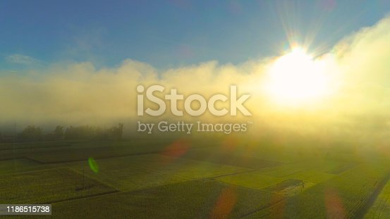AERIAL: Flying through dense morning fog above meadow fields, revealing sun against the clear blue sky. Cold morning clouds clearing over farmland, warm golden sun and blue skies appearing.