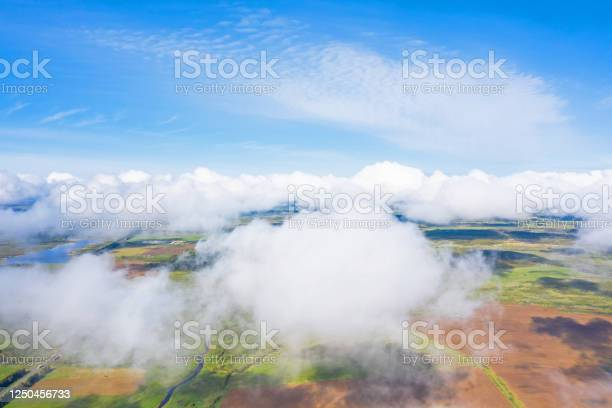 Photo of Flying through the fluffy clouds layers. Camera above ground. Amazing soft white clouds moving slowly on the clear sky