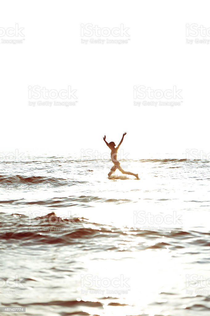 Flying through the waves. Happy girl jumping in the sea. stock photo