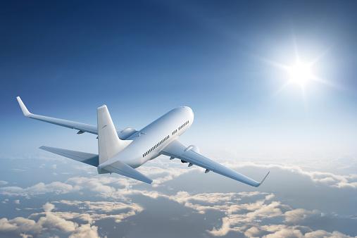 Airplaine flies above the calm cloudscape towards the sun.