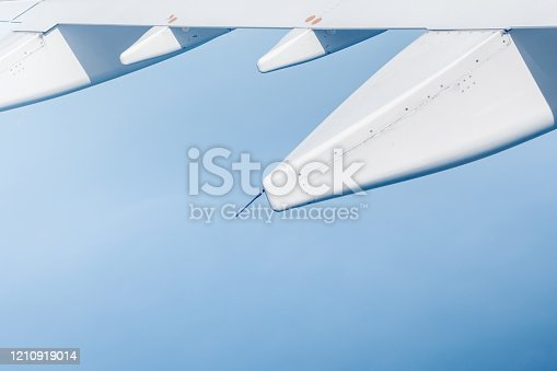902818356 istock photo flying wing of a commercial airplane that is flying on the sky 1210919014