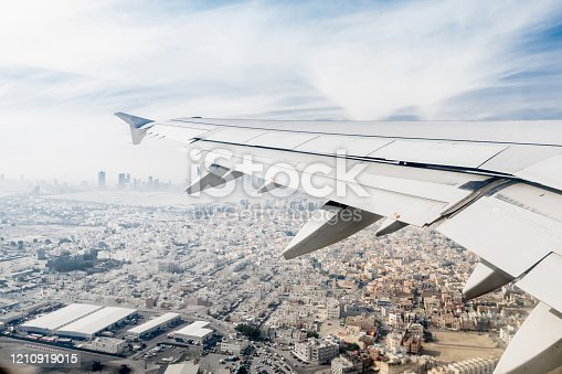 902818356 istock photo flying wing of a commercial airplane that is flying on the sky 1210919015