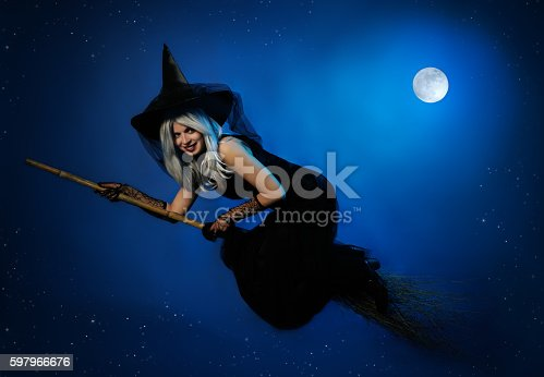 istock flying witch with a broom 597966676