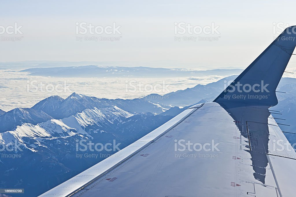 Flying with jet airplane over Alps in morning stock photo