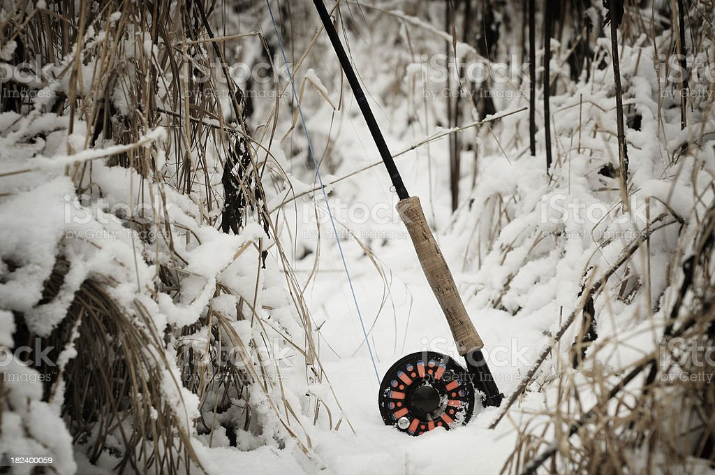Flyrod and reel on snowy river bank stock photo