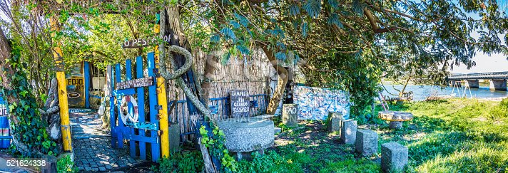 Fão, Portugal - April, 17th 2016: Fão alongside the river Cavado in Portugal with this abandoned restaurant hideout, dedicated to the sailors, under a large tree. Fao is situated in the north of Portugal with the beach of Ofir.