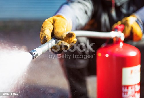 Close up as a foam fire extingusher is used.