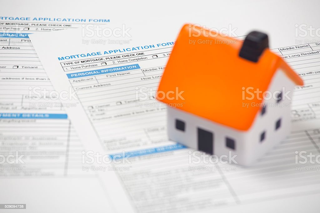 foam house on top of mortgage application form stock photo