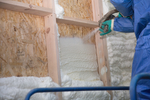 Foam is applied to the walls to warm the house at construction