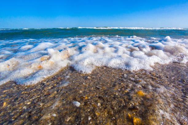 schaum auf den kamm der meerwelle vor einem blauen himmel. meereswellen rollen auf ans ufer. meerschaum. stürmische see. closeup - roll tide stock-fotos und bilder