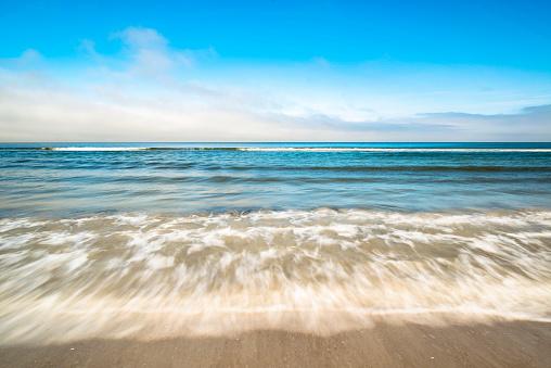 Schäumende Wellen treffen auf den Strand.