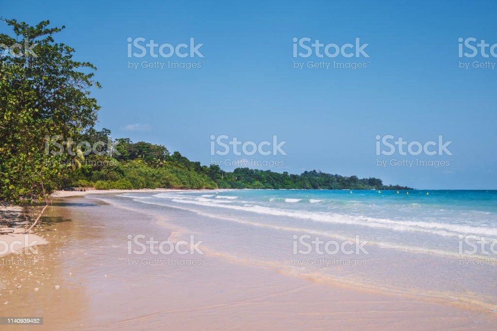 Flache, klare Ozeanwellenrollen zu rosa Sand Shore türkisfarbenes blaues Wasser. – Foto