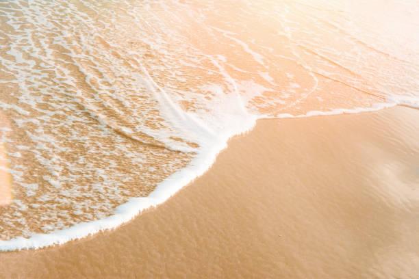 schäumend klaren meer welle rollt am goldufer sand rosa sonne flare pastell-farben. schöne ruhige idyllische landschaft. ocean beach entspannung urlaubsparadies. textfreiraum - roll tide stock-fotos und bilder