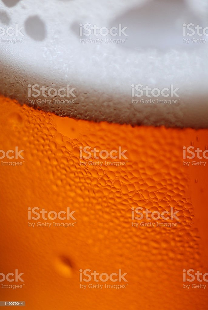 Foamy head on rich amber beer closeup stock photo