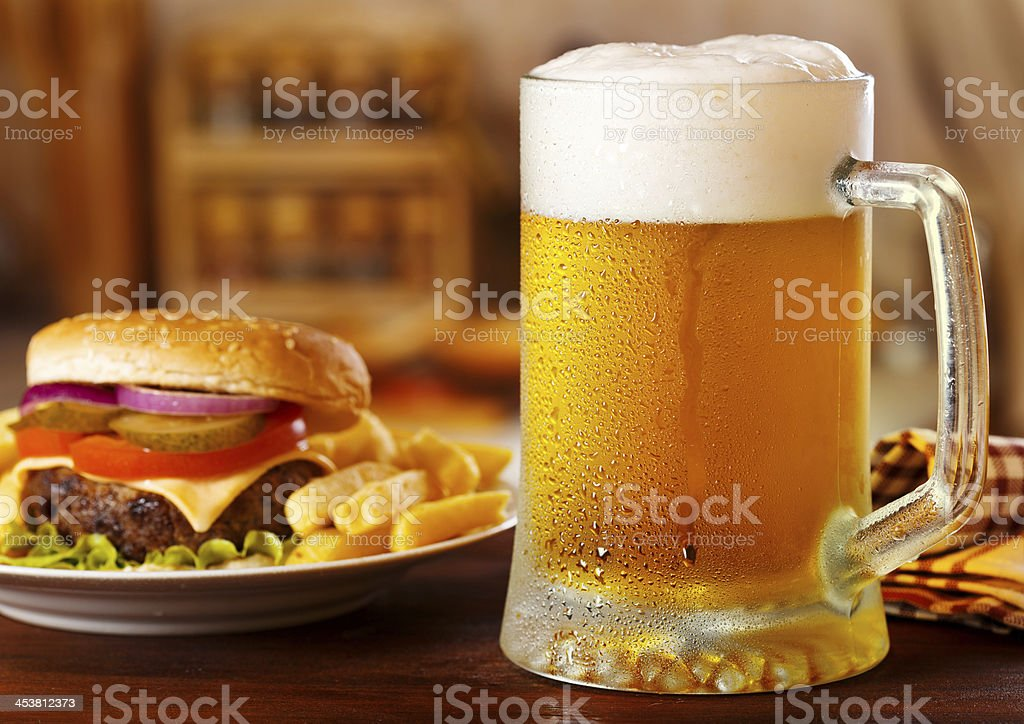 Foamy mug of beer next to cheeseburger with fries on table stock photo