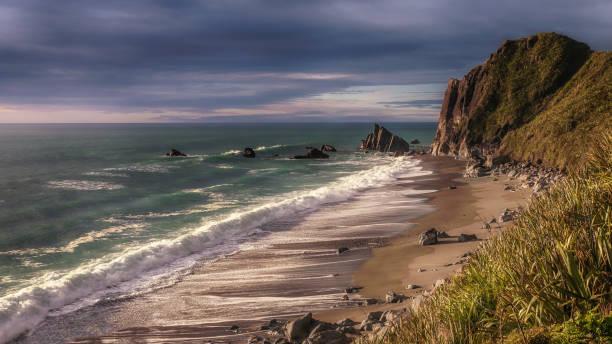 schäumende welle brechen auf leer, abgelegenen strand bei flut auf neuseelands südinsel. - roll tide stock-fotos und bilder