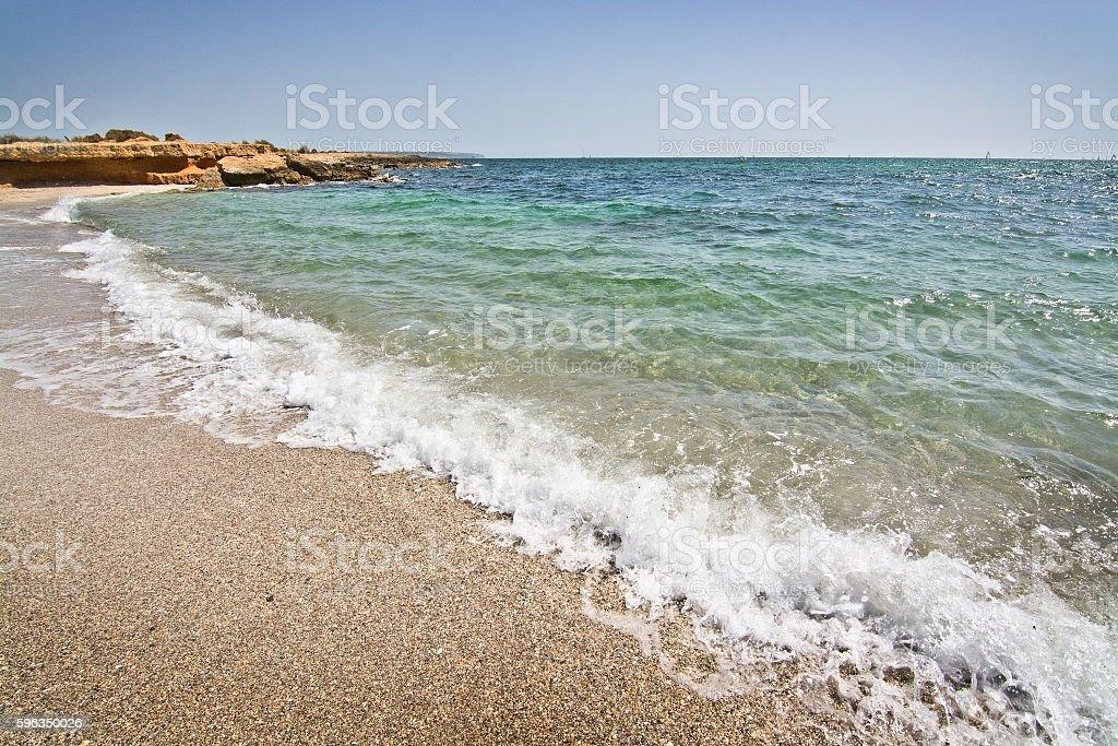 Foamy wave hits rocks and seashells beach royalty-free stock photo