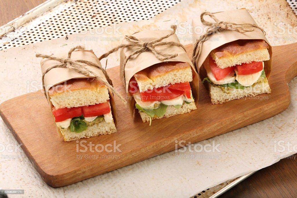 Focaccia sandwich with mozzarella basil and tomato on a chopping stock photo