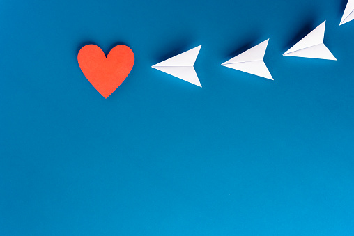 istock Focus, assertiveness, work yourself concept. Paper heart shape with airplane on blue background 1172990954